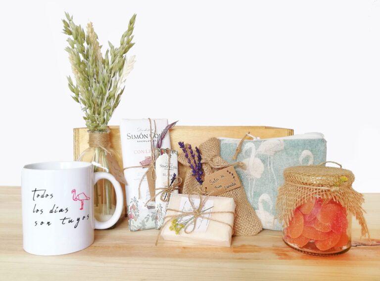 Pack regalo compuesto por diferentes elementos como taza, jarron flores, chuches, jabon, sales de baño y neceser hecho a mano en una caja de madera.