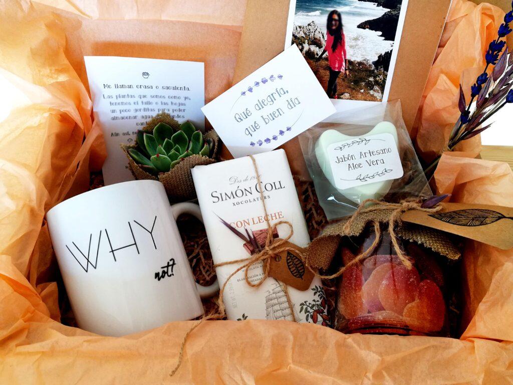 Pack regalo compuesto por taza, libreta kraft, planta decorada, tableta de chocoalte, botecitos de chuches y jabón artesanal.