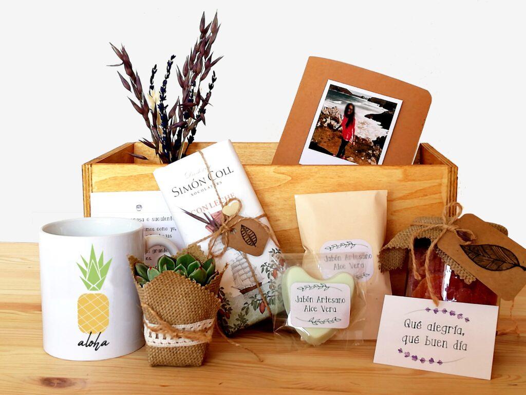 Pack regalo compuesto por taza, libreta kraft, planta decorada, tableta de chocoalte, botecitos de chuches y jabón artesanal en caja de madera
