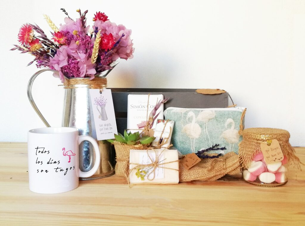 Caja De madera con arreglo de flores, taza de ceramica, neceser, plantita, jabon artesanal, y mas elementos.