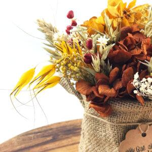 Centro de flores preservadas en cesto de yute en bandeja de madera