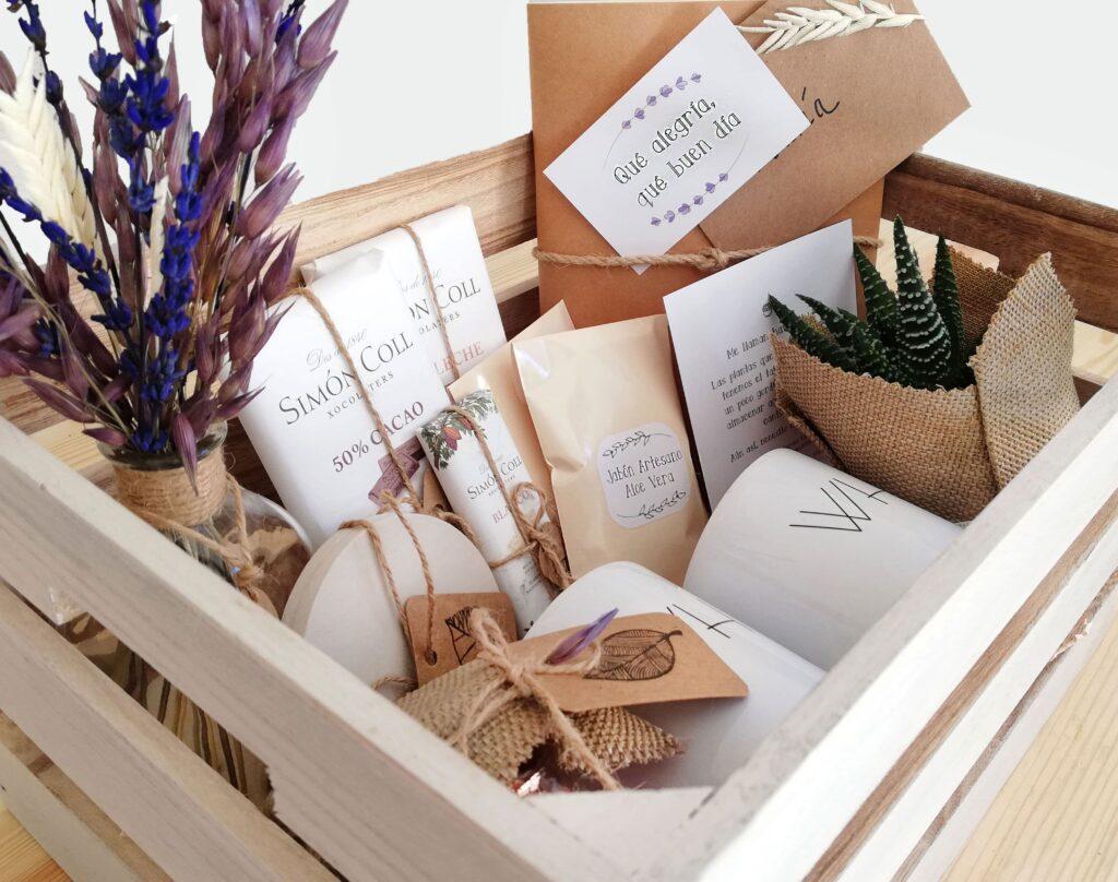 Pack regalo formado por Caja de Madera, tazas con mesaje, libreta kraft, chocolates, y más elementos.