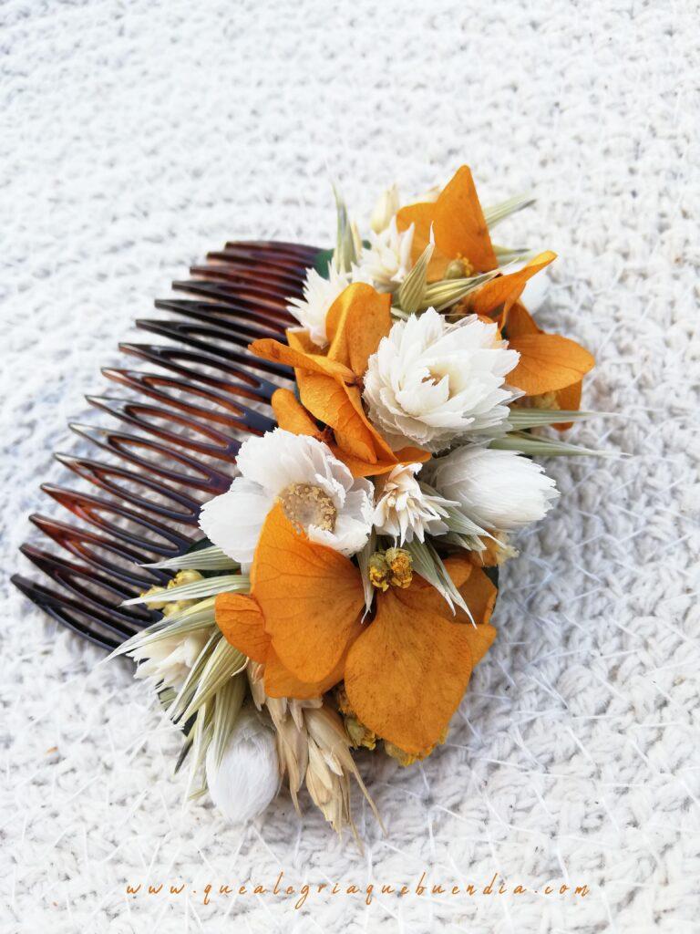 Tocados floral en peineta marrón decorada con flores preservadas en tonalidades amarillas y blancas.