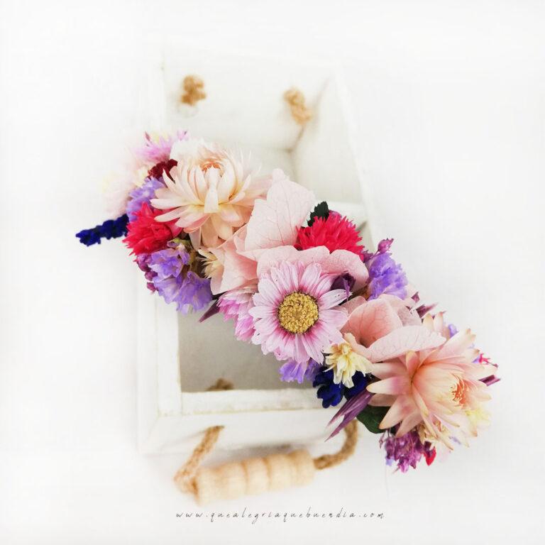 Diadema decorada con Flores Preservadas en diferentes tonalidades encima de caja blanca.