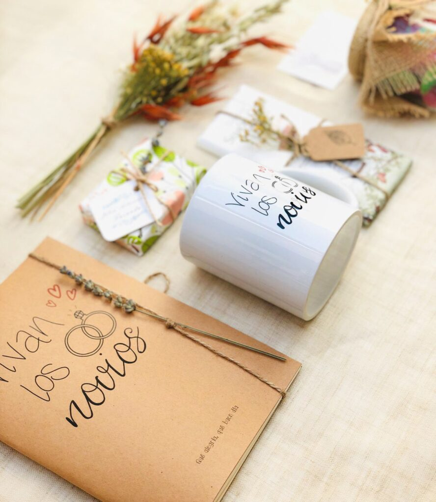 Pack Regalo Novias 1compuesto por taza con mensaje, libreta Kraft, jabon artesanal, chocolate, y chuches