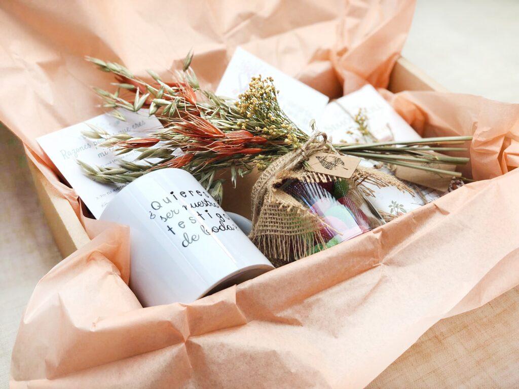 Pack regalo bodas compuesto por taza, chuches, chocolate, libreta kraft y decoración extra.