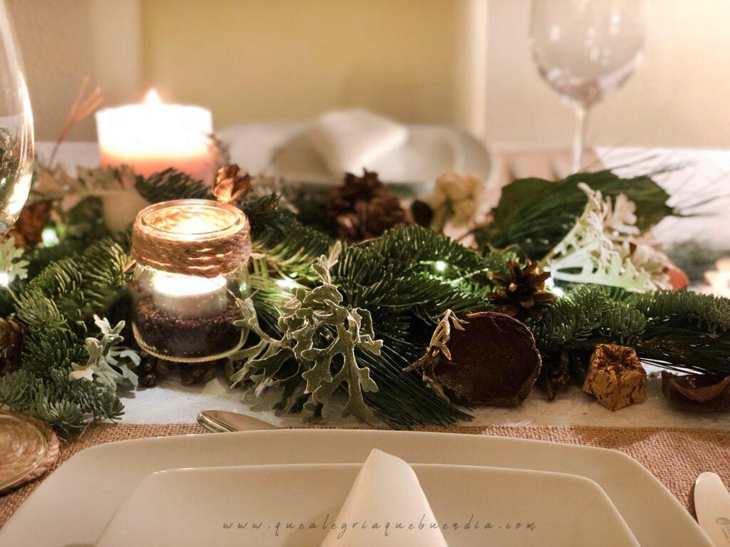 Decoracion Mesa Navidad compuesta por diferentes ramas verdes, velas, piñas, y más elementos decorativos.