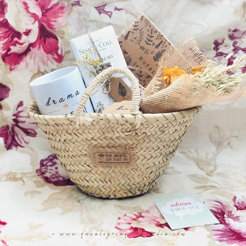 MiniPack Capazo regalo ideal para el amigo invisible. Esta compuesto por capazo de mimbre, taza, chocolate, libreta y ramo de flores. Regalos hechos a mano