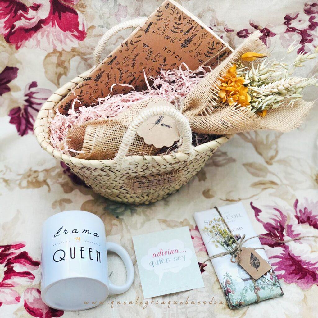 MiniPack Capazo regalo ideal para el amigo invisible. Esta compuesto por capazo de mimbre, taza, chocolate, libreta y ramo de flores. Regalos diferentes