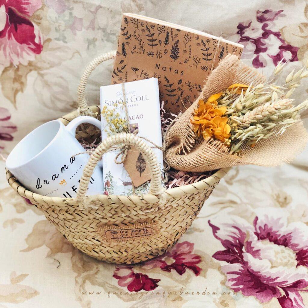MiniPack Capazo regalo ideal para el amigo invisible. Esta compuesto por capazo de mimbre, taza, chocolate, libreta y ramo de flores. Regalos personalizados