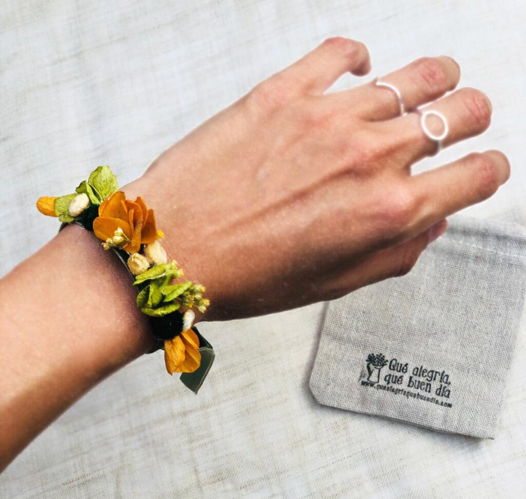 Foto de una pulseras flor preservada en la mano para regalar a testigos
