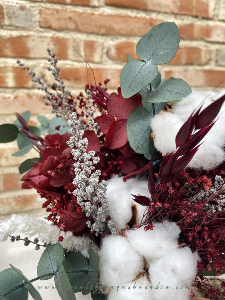 Ramo de flores preservadas en tonos burdeos, blancos, y verdes. Detalles