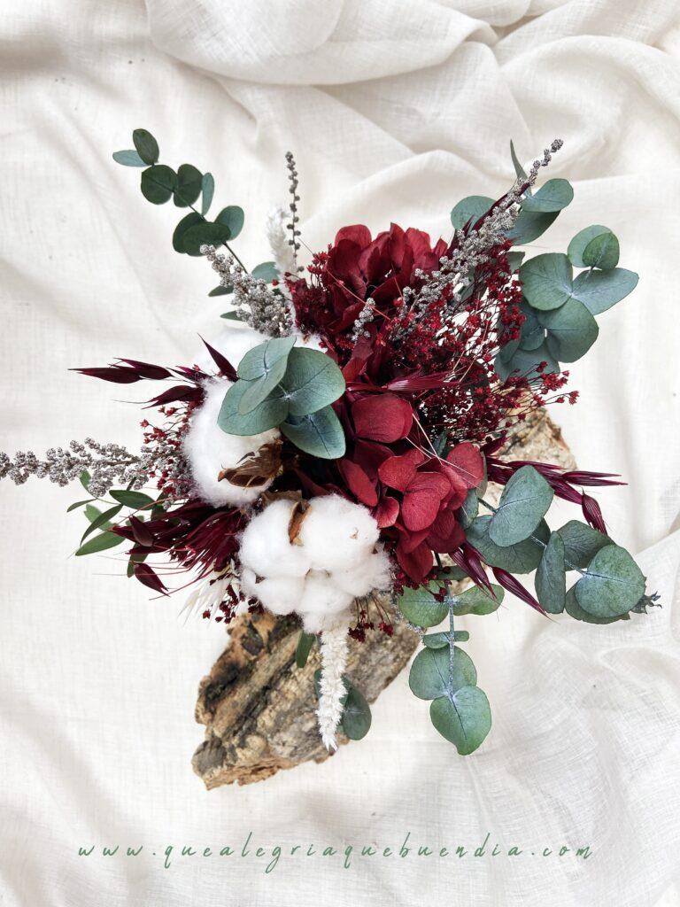 Ramo de flores preservadas en tonos burdeos, blancos, y verdes. Vista desde Arriba