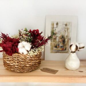 Cesto de flores preservadas en tonos burdeos en cesta de mimbre