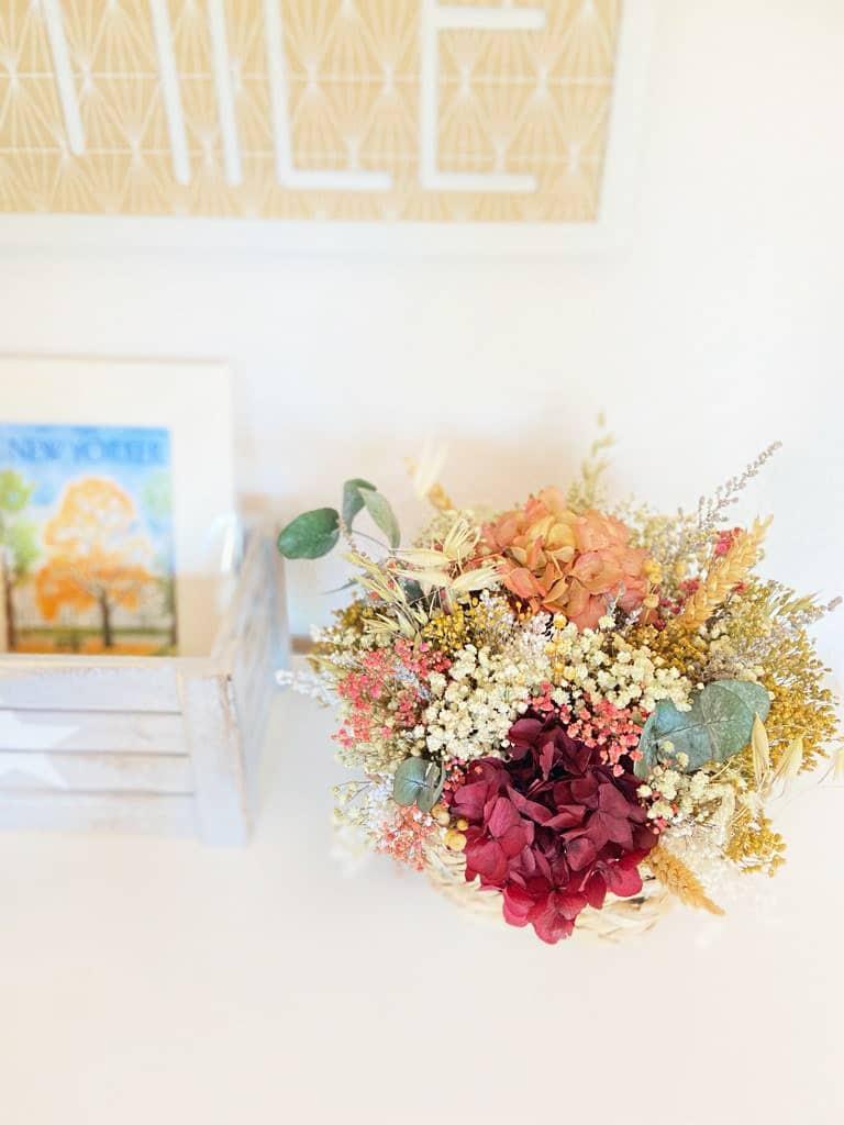 Centro de flores Preservadas Mimbre Moira en tonos rosados, cramas, blancos y tostados en cesto de mimbre en la habitación