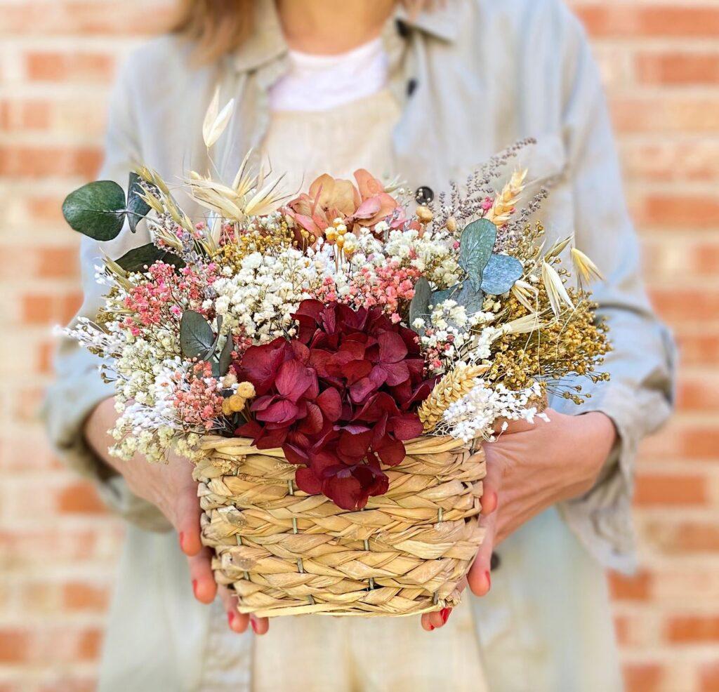 Centro de flores Preservadas Mimbre Moira en tonos rosados, cramas, blancos y tostados en cesto de mimbre