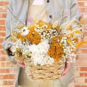 Centro de flores Preservadas Mimbre Tonos Amarillos Regalo ideal para decorar tu hogar. Esta hecho con flores preservadas en tonos amatillos. La foto aparece el centro agarrado con las manos.