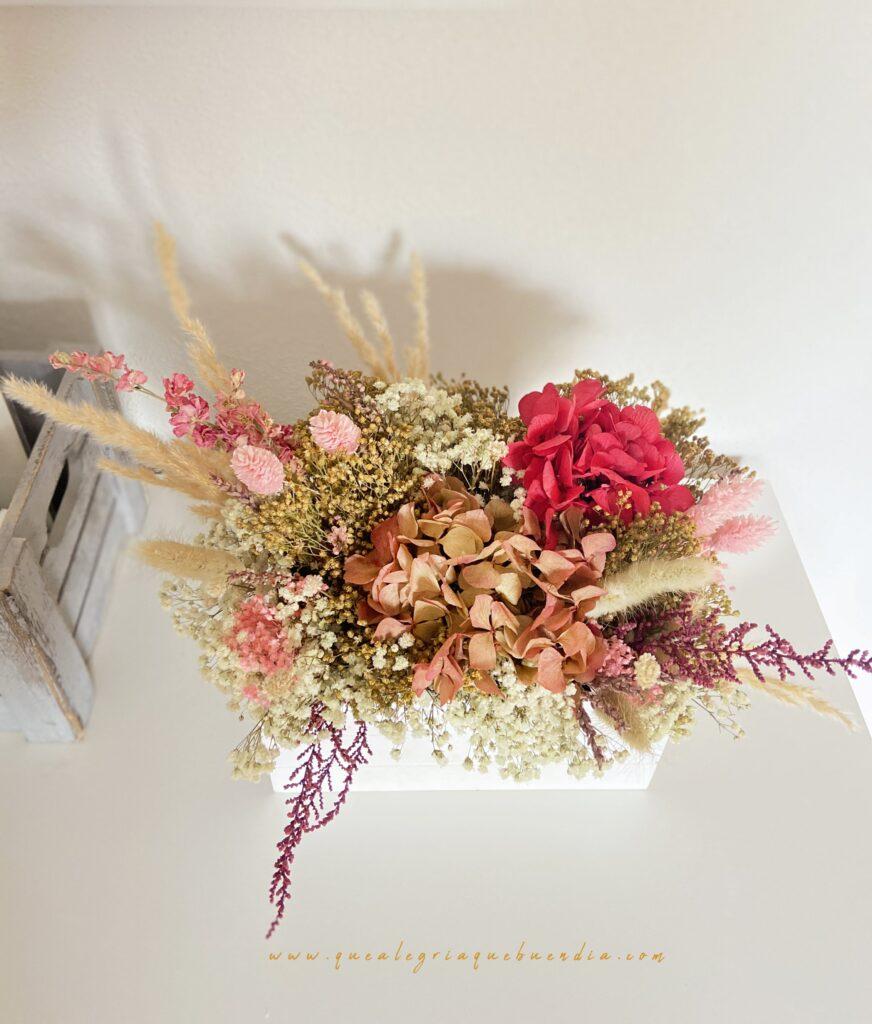 Centro de flores preservadas en tonos rosados en caja de madera blanca