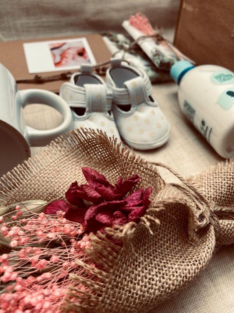 Pack regalo para un recien nacido con diferentes elementos personalizados y zapatitos de bebé