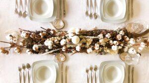Vista desde arriba de la decoración mesa navidad en tonos cremas blancos marrones y tostados hechas con flores y ramajes