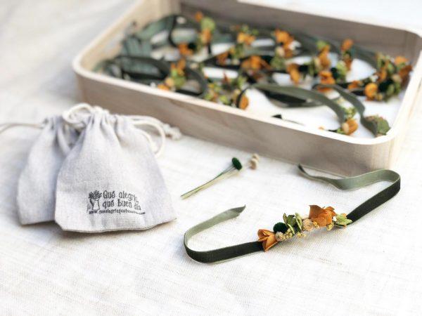 Foto de muchas PULSERAs de flor preservada en una bandeja para regalar a testigos