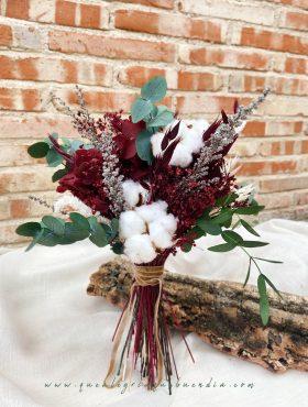 Ramo de flores preservadas en tonos burdeos, blancos, y verdes.